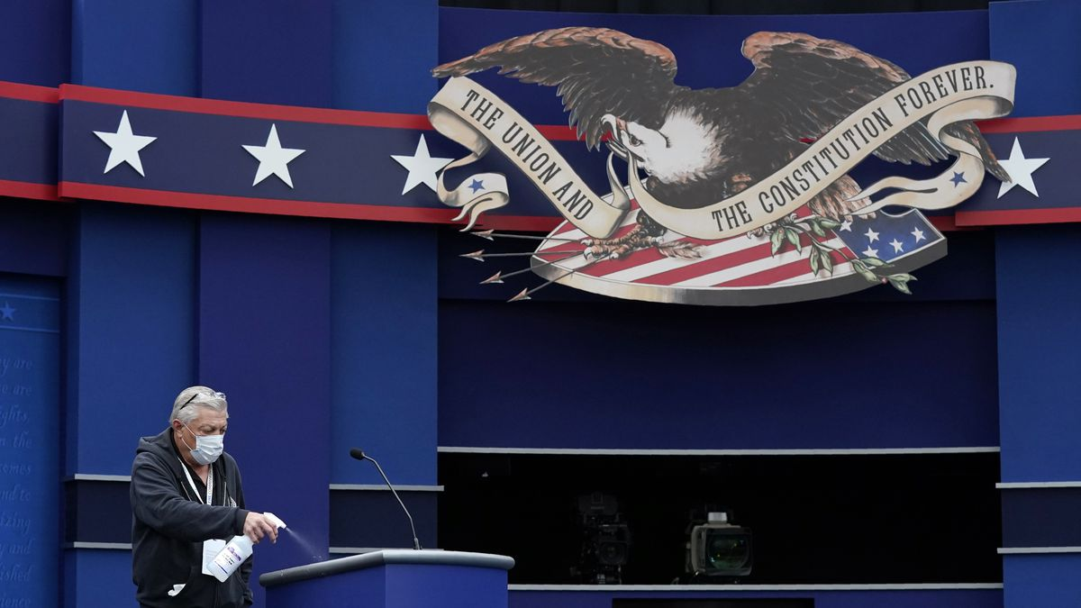 A worker sprays sanitizer on a lectern as preparations take place for the first Presidential debate in the Sheila and Eric Samson Pavilion, Monday, Sept. 28, 2020, in Cleveland. The first debate between President Donald Trump and Democratic presidential candidate, former Vice President Joe Biden is scheduled to take place Tuesday, Sept. 29.