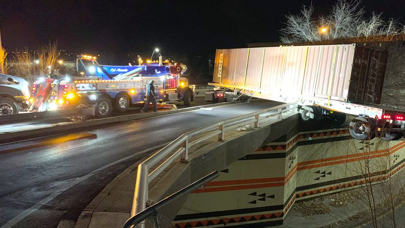 The end of a tractor-trailer hangs over a Keystone Avenue bridge after the vehicle turned onto...