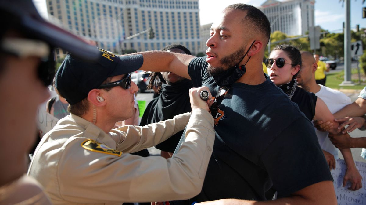 Police officers move back people Friday, May 29, 2020, as they march on Las Vegas Boulevard in Las Vegas, while protesting the death of George Floyd, who died while in Minneapolis police custody. (AP Photo/John Locher)