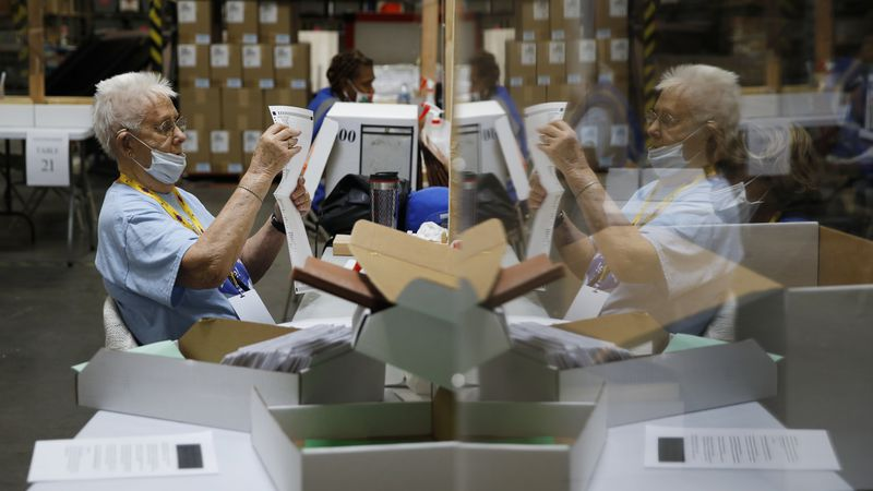 In this June 9, 2020, file photo, election workers process mail-in ballots during a nearly...