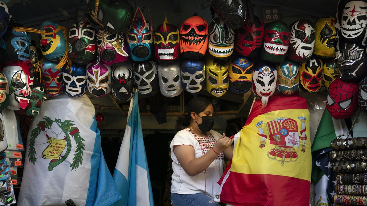 Clerk Wendy Ramirez uses a Spanish flag to wrap souvenirs while preparing to close the store...