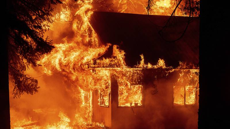 Flames consume a home as the Dixie Fire tears through the Indian Falls community in Plumas...