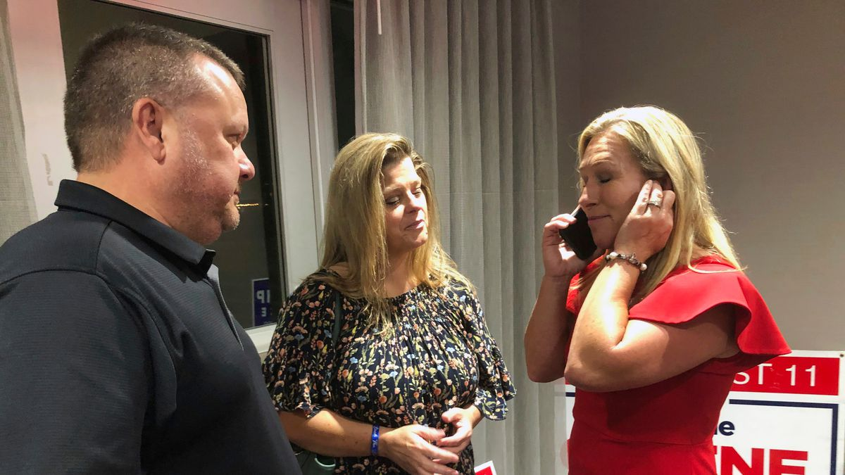 Supporters stand with construction executive Marjorie Taylor Greene, right, as she's on the phone, late Tuesday, Aug. 11, 2020, in Rome, Ga.