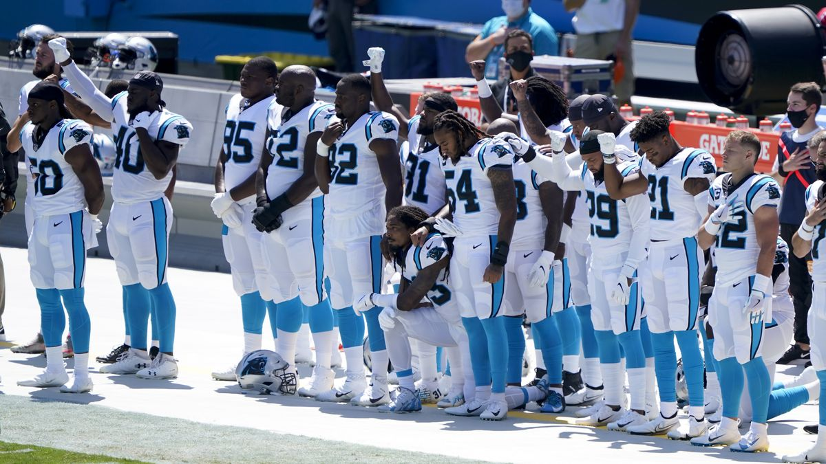 Members of the Carolina Panthers gesture during the Nation Anthem before an NFL football game...