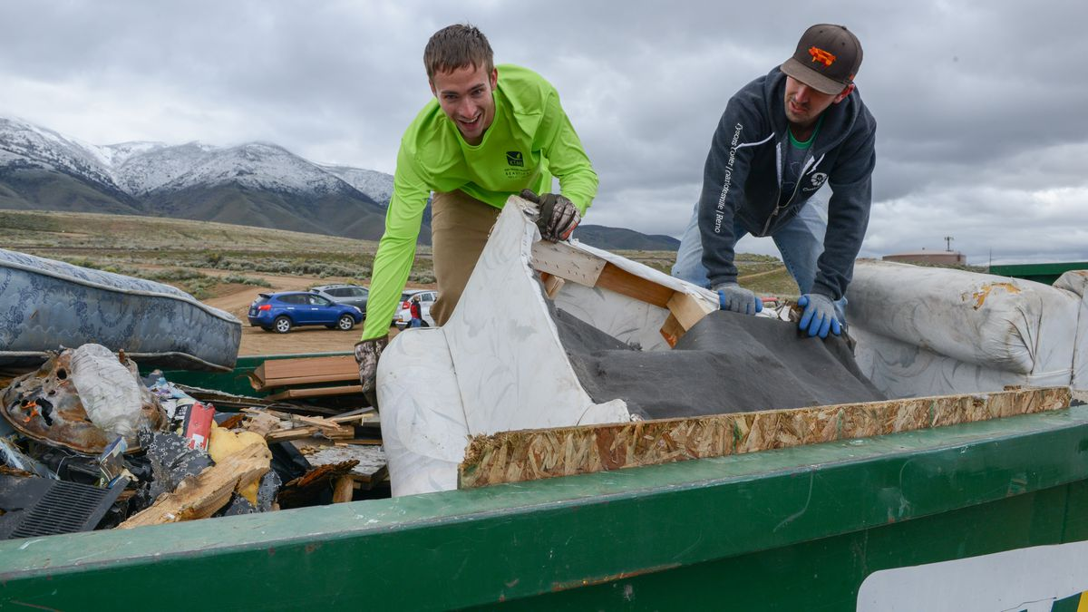 Daniel Gray, left, and Anthony Sawyer stuff the dumpster during the Keep Truckee Meadows...