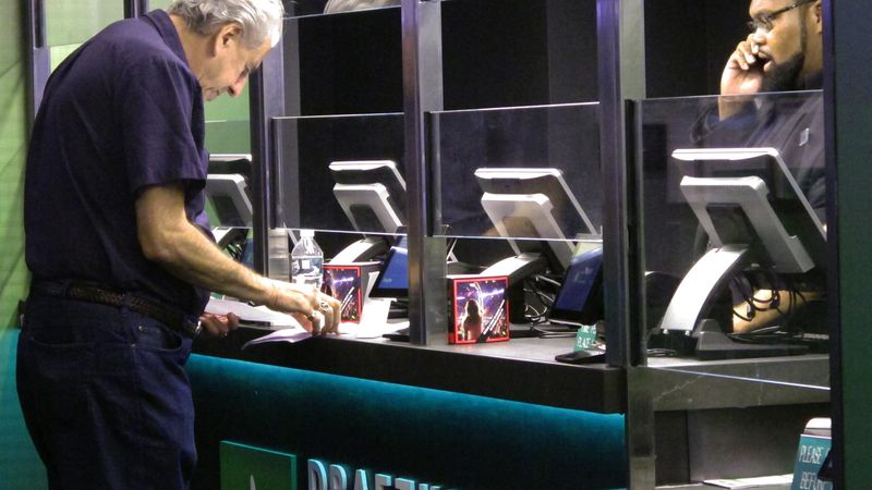 In this Oct. 8, 2019 photo, a customer makes a sports bet at the DraftKings sports book at...