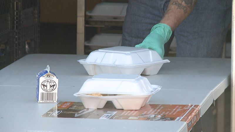 A server puts to-go meals out for those in need