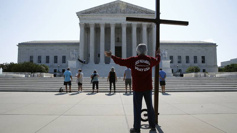 Tom Alexander holds a cross as he prays prior to rulings outside the Supreme Court on Capitol...
