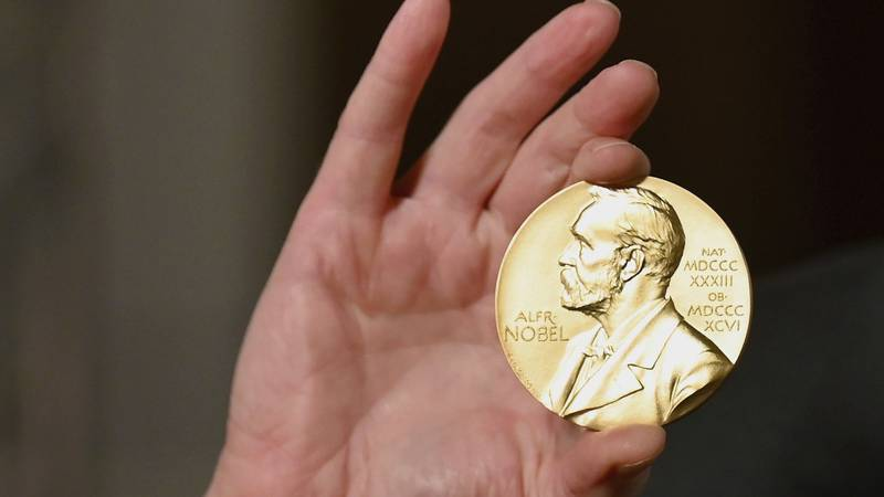 FILE - In this Tuesday, Dec. 8, 2020 file photo, a Nobel medal is held up during a ceremony in...