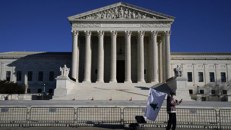 A person walks by newly-placed barricades around the Supreme Court Building the day after...