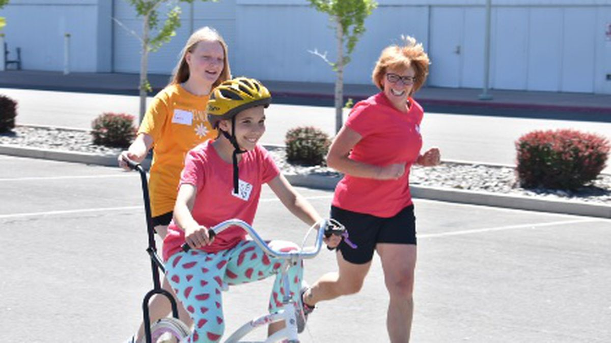 Volunteers are teaching a girl with developmental disabilities learn how to ride a conventional...