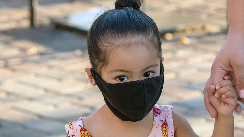 Child wearing a cloth face mask.