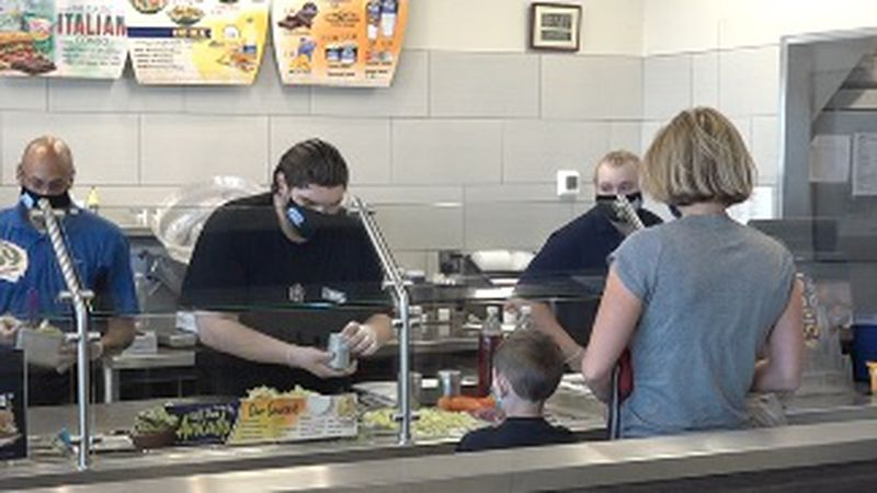 A Port of Subs employees prepares meal for a customer.