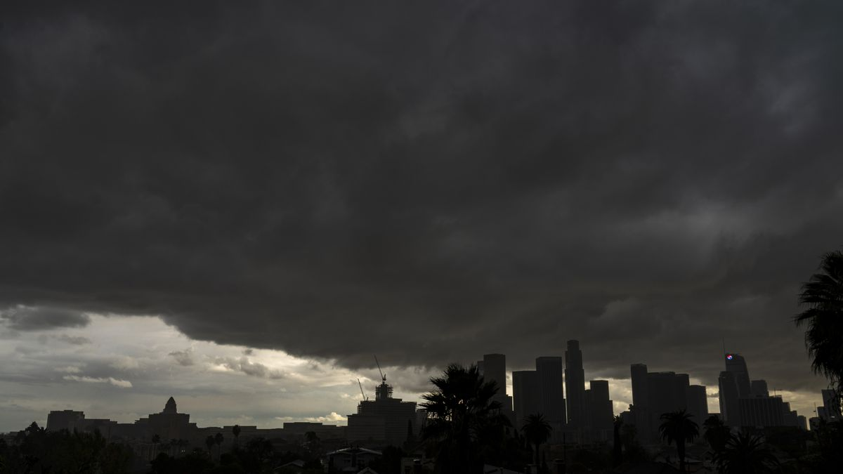 Heavy clouds move over Los Angeles city skyline Saturday, Jan. 23, 2021. Rain and snow showers...