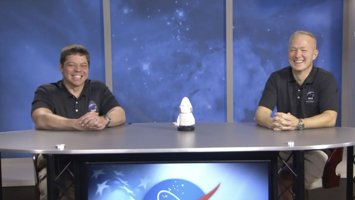 In this frame grab from NASA TV video, astronauts Bob Behnken, left, and Doug Hurley laugh during a news conference, Tuesday, Aug. 4, 2020, in Houston. The two NASA astronauts returned to Earth on Sunday in a dramatic, retro-style splashdown carried out by Elon Musk's SpaceX company.