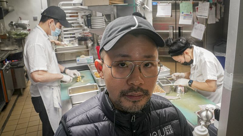 Korean American chef Douglas Kim, center, owner of the restaurant Jeju, which was vandalized...