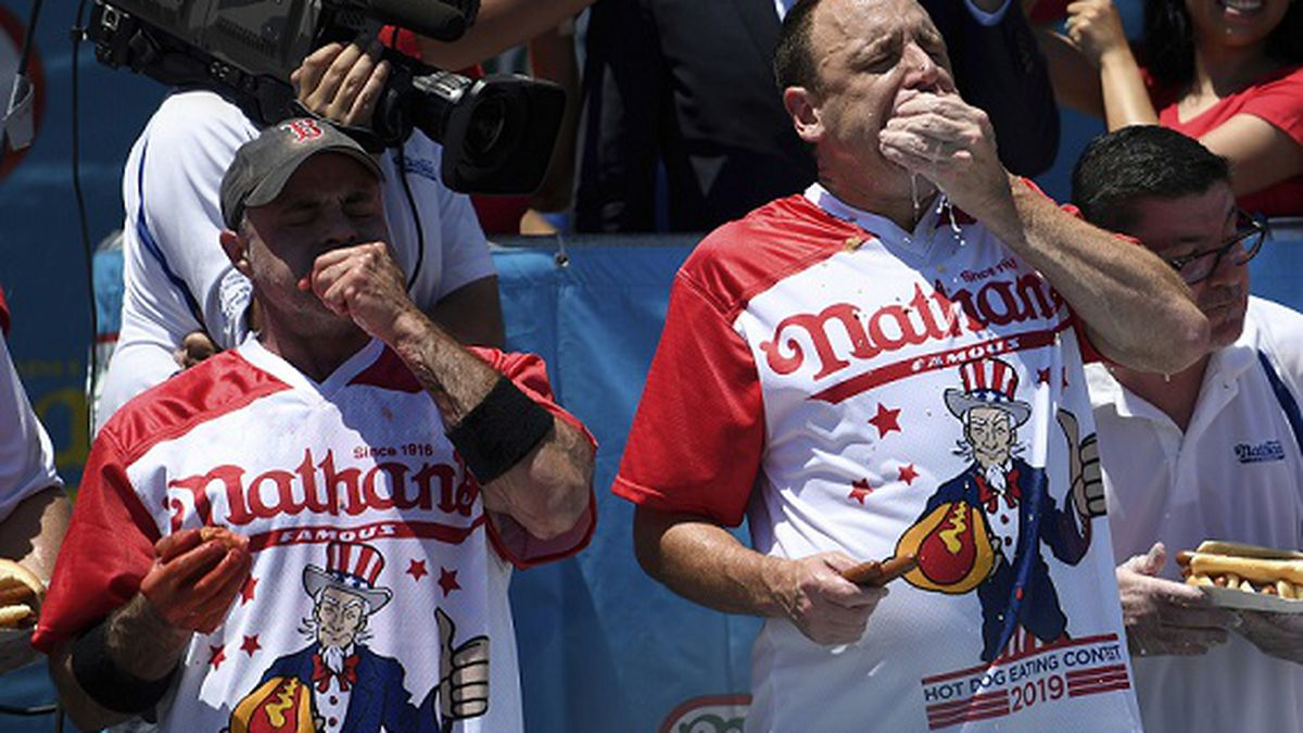 Geoffrey Esper, left, and Joey Chestnut, right, compete during the men's competition of Nathan's Famous July Fourth hot dog eating contest, Thursday, July 4, 2019, in New York's Coney Island. (AP Photo/Sarah Stier)
