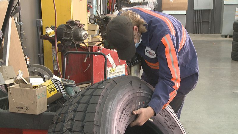 An employee at Purcell Tire puts studs on a tire to prepare it for winter conditions
