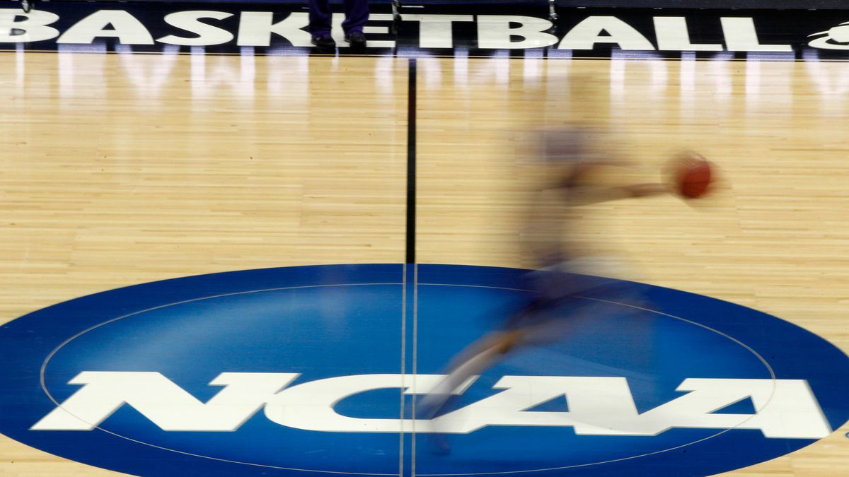 FILE - In this March 14, 2012 file photo, a player runs across the NCAA logo during practice in...