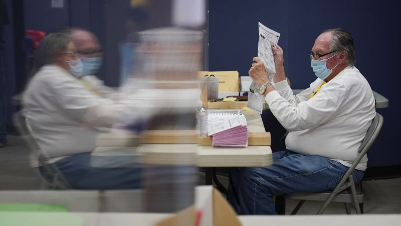FILE - In this Oct. 31, 2020, county employees process mail-in ballots at a Clark County...