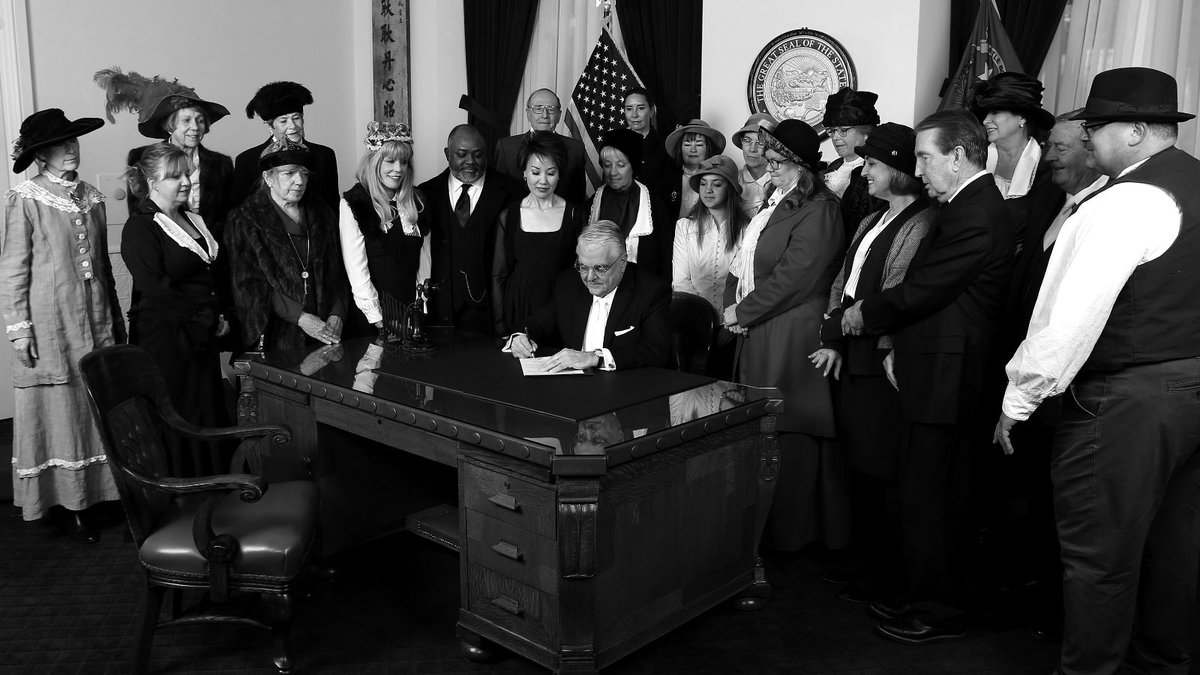 Nevada Gov. Steve Sisolak and others recreate a photo of when women were given the right to...