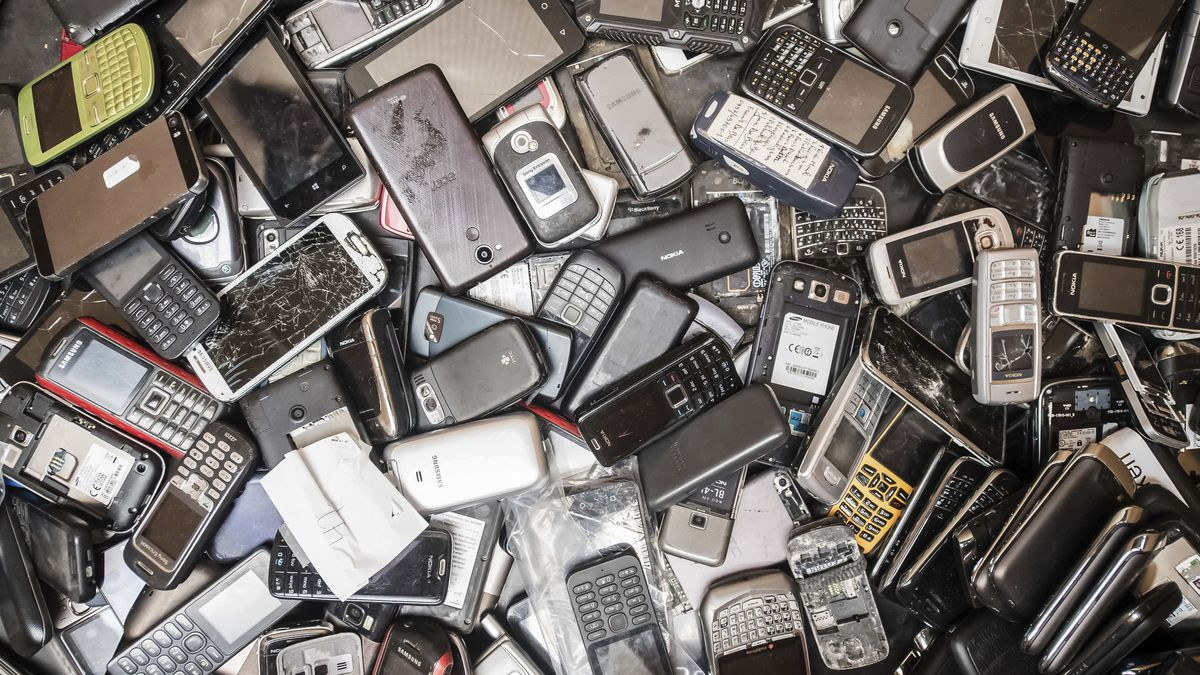 In this photo taken on July 13, 2018, old mobile phones fill a bin at the Out Of Use company...
