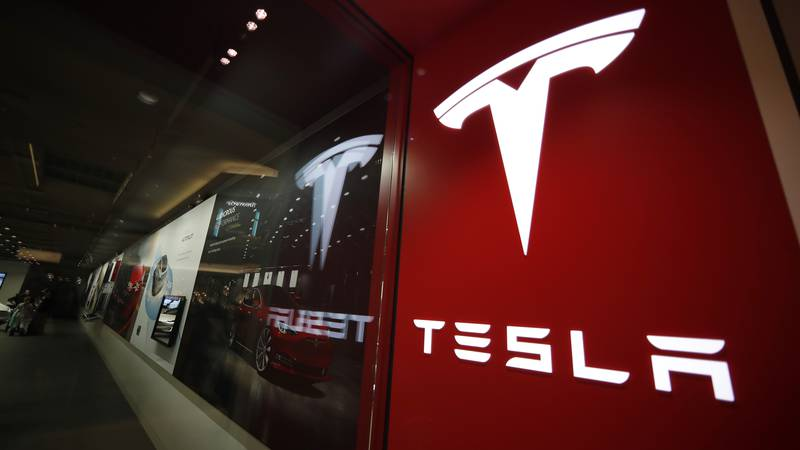 This Feb. 9, 2019, file photo shows a sign bearing the company logo outside a Tesla store in...