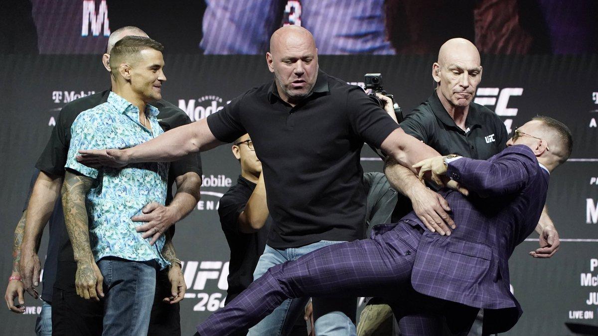 Conor McGregor, right, kicks at Dustin Poirier, left, as Dana White, UFC President, holds them...