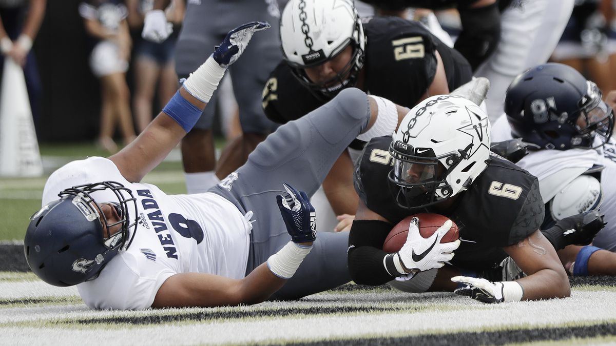 Vanderbilt running back Josh Crawford (6) scores a touchdown on a 1-yard run against Nevada in the second half of an NCAA college football game Saturday, Sept. 8, 2018, in Nashville, Tenn. Defending for Nevada is linebacker James Fotofili (8). Vanderbilt won 41-10. (AP Photo/Mark Humphrey)