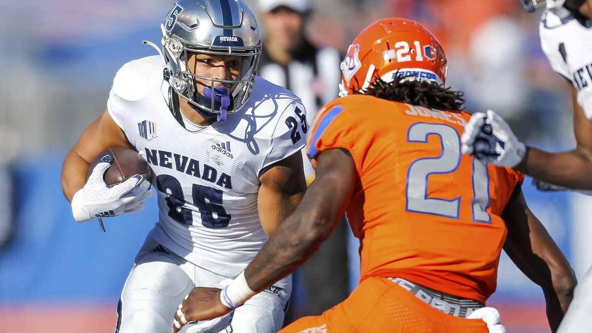 Nevada running back Avery Morrow (25) runs with the ball as Boise State safety Tyreque Jones...