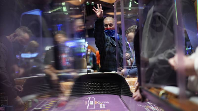 In this March 25, 2021, file photo, people play craps while wearing masks between partitions at...