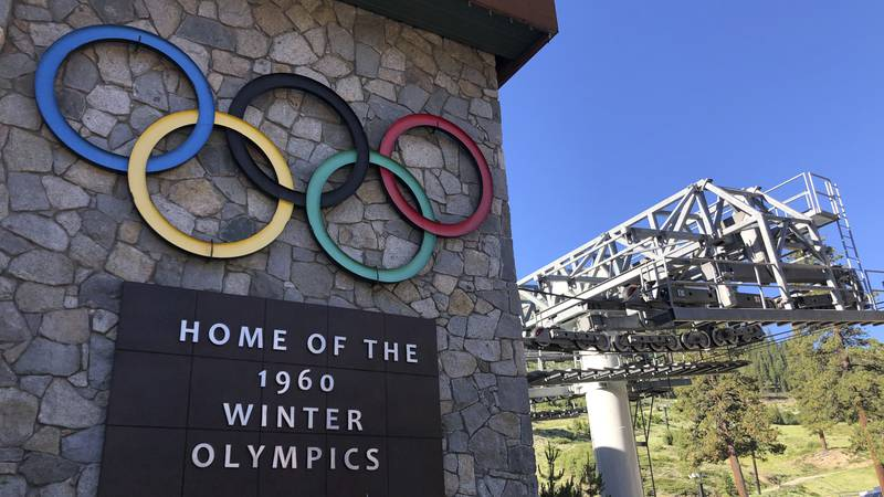 In this July 9, 2020, file photo, a sign marking the 1960 Winter Olympics is seen by a...
