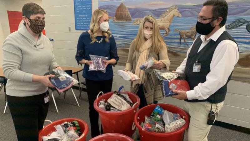 Alice Smith Elementary School staff hold clothing items donated for students.